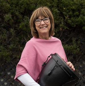 Elizabeth Bolwell, smiling, holding a djembe drum
